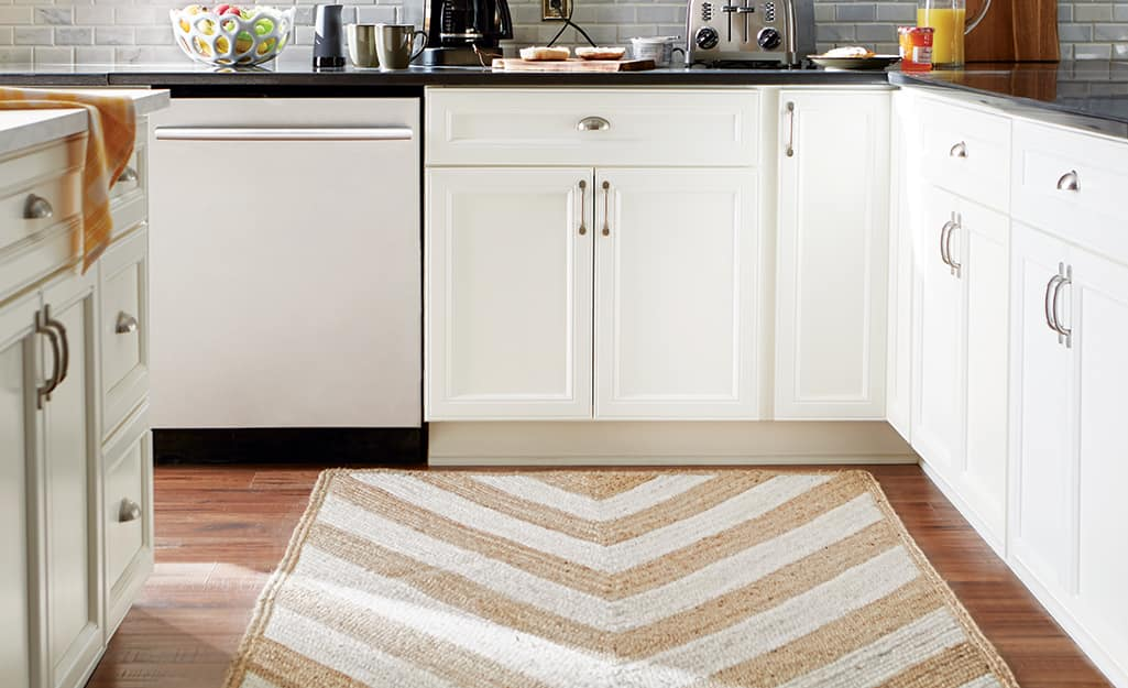 A beige and tan chevron-stripe rug in a kitchen.