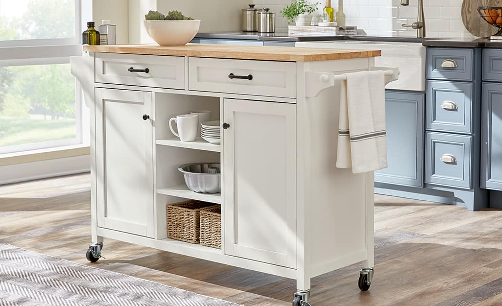 A white kitchen cart with a butcher block top.