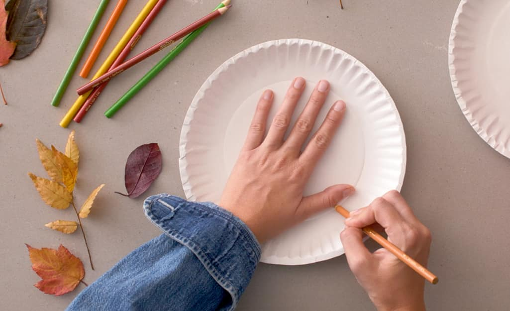 A person traces their hand on a paper plate.