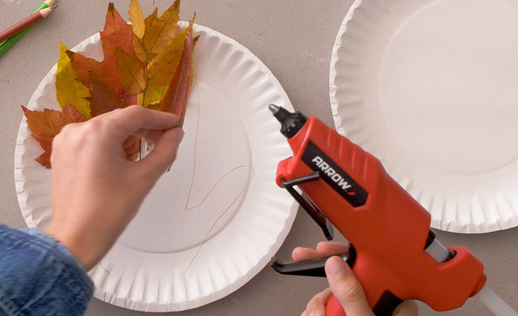 A person uses a glue gun to glue leaves to a paper plate.
