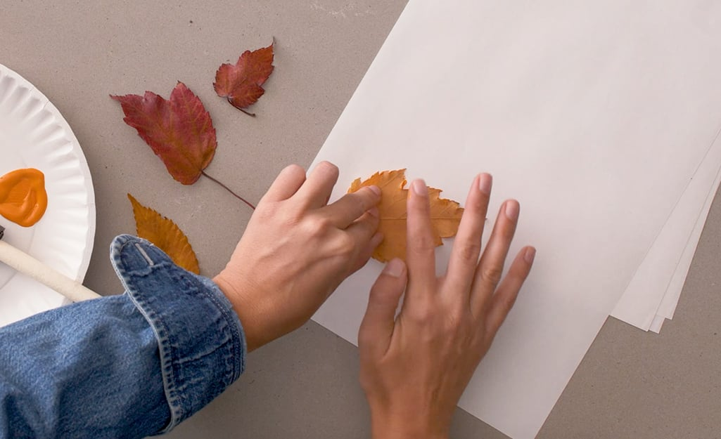 Painted leaves are pressed onto paper.