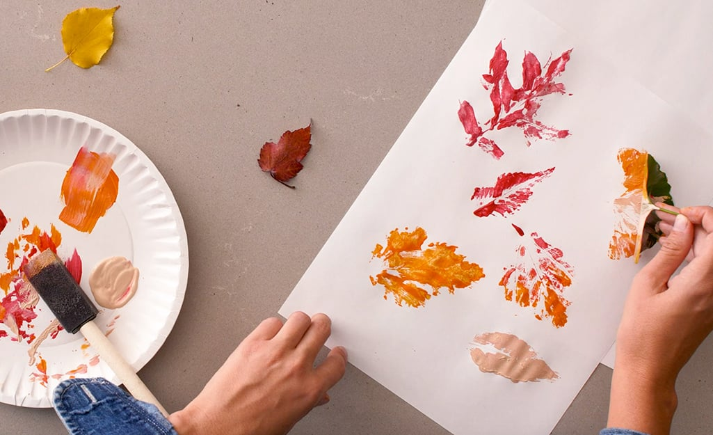 Painted leaf prints on construction paper.