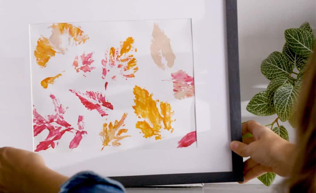 Leaf stamp art is framed and placed on a shelf.