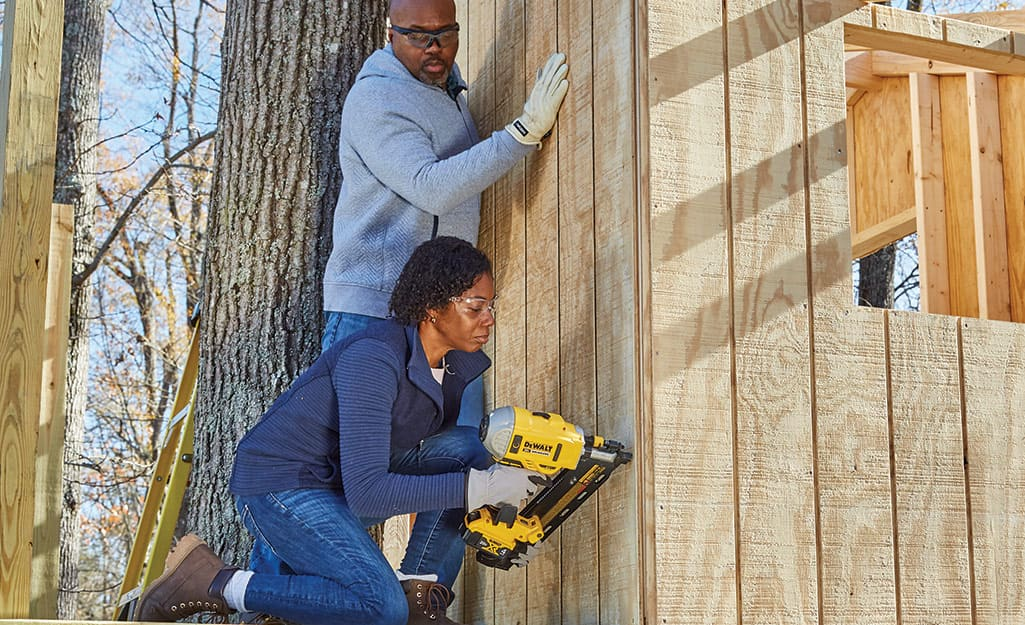 Couple attaches siding to a treehouse frame.