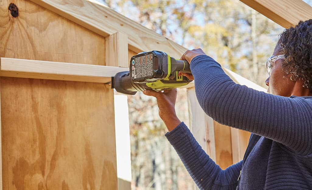 A woman uses a reciprocating saw to cut holes for doors and windows.