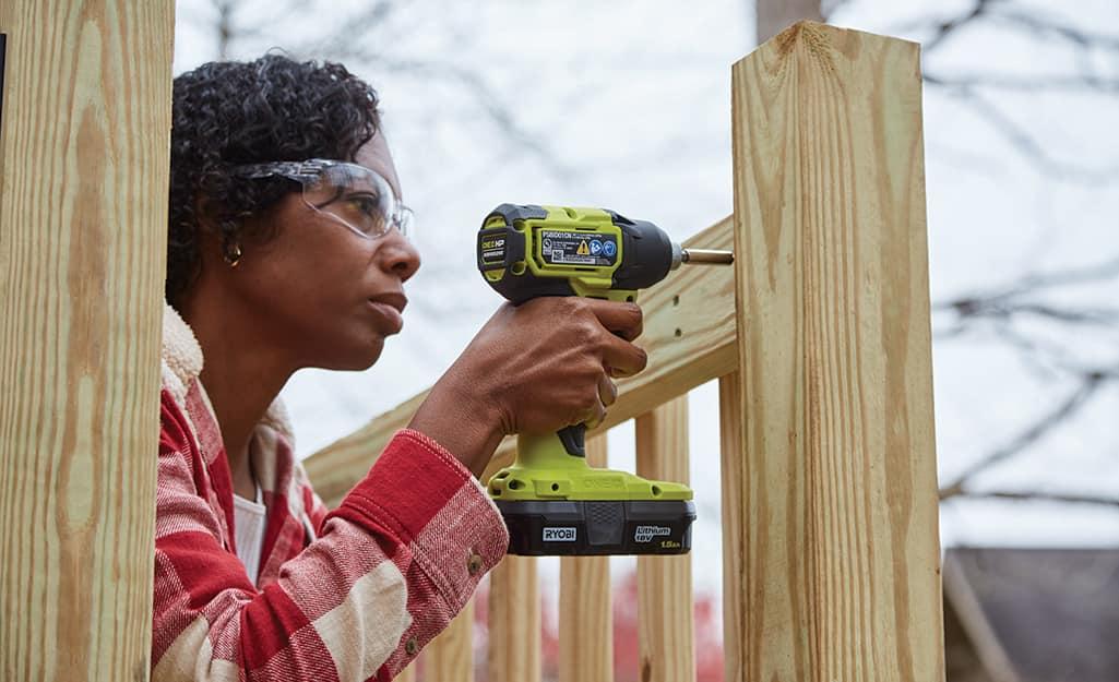 A woman attaches a handrail.