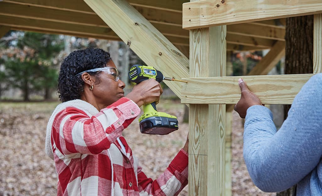 A woman attaches a ladder to the treehouse.