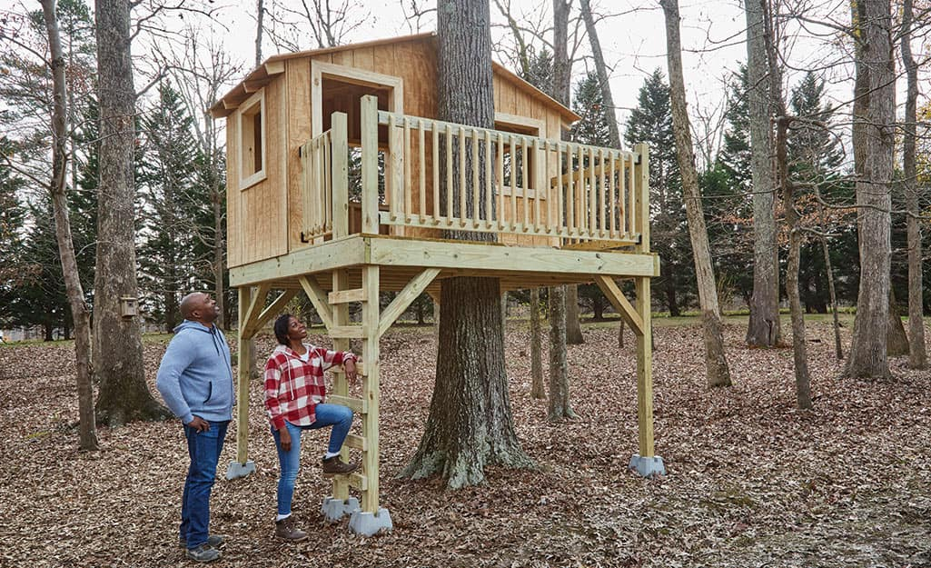 A couple admires their finished treehouse.