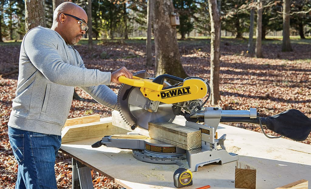 A man uses a miter saw to cut angle braces from 4 x 4's.