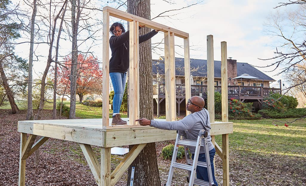 A couple builds the frame for a treehouse.