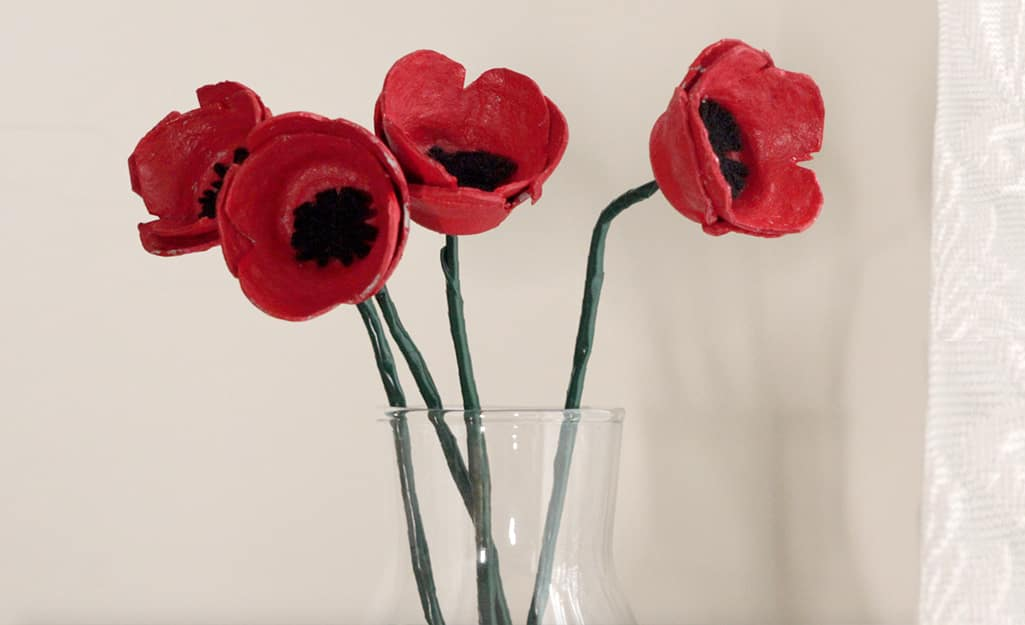 Four paper poppies sit in a vase.