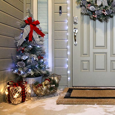 A front entryway with an artificial Christmas tree and Christmas decorations.