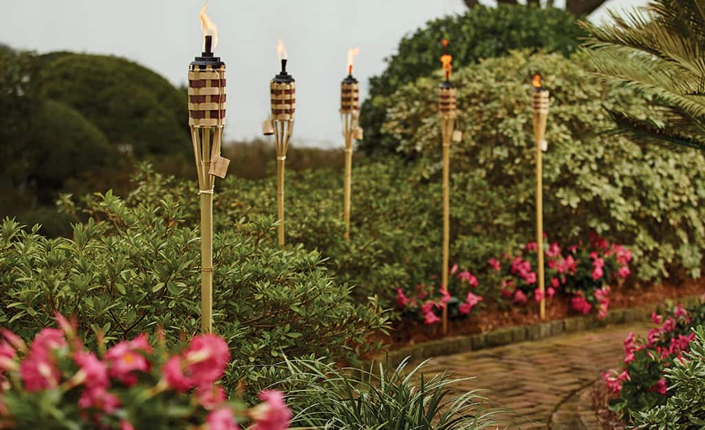 Tiki torches in a flower bed by a paver path