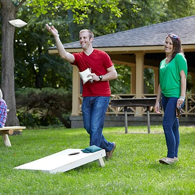 A couple plays a game of cornhole at a backyard tailgate.