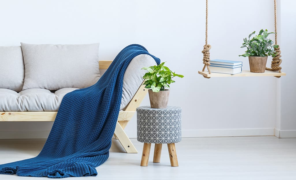 A blue blanket on a white sofa with houseplants