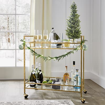 A bar cart with assorted drinks and a mini Christmas tree.