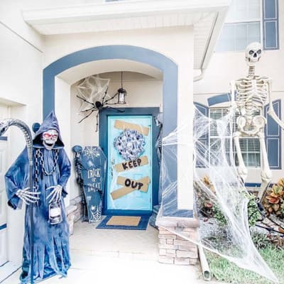 A blue and white front porch decorated for Halloween with a grim reaper.