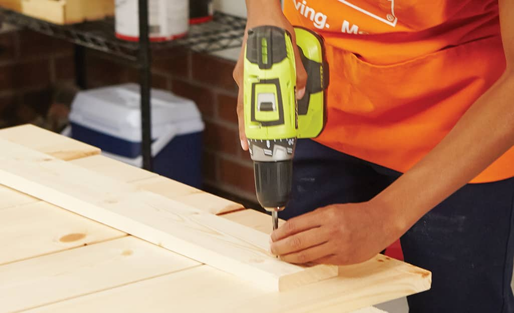 a person screwing pieces of plywood to each other