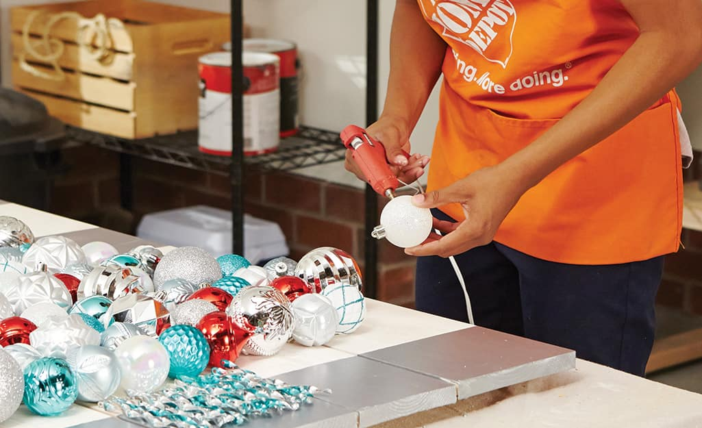 a person using a glue gun to stick ornaments on a pallet