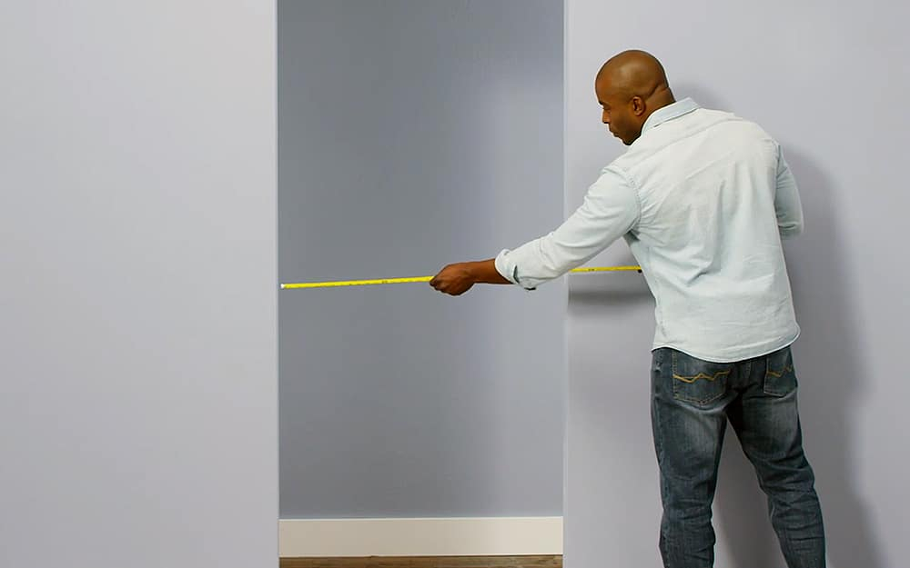 A man uses a tape measure on a doorway.