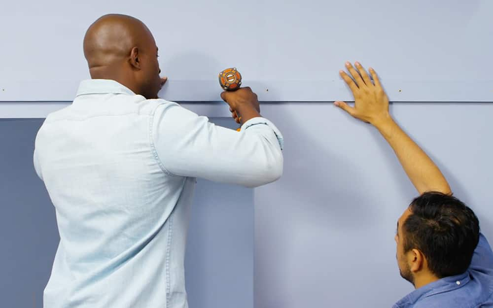 Two workers attach door moulding to a wall.
