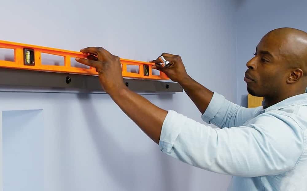 A person uses a level to check the barn door's track.