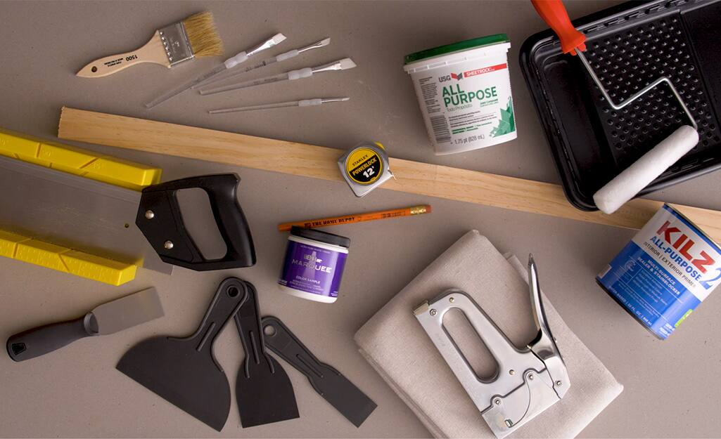 Miter box, staple gun and other supplies lay on a table.