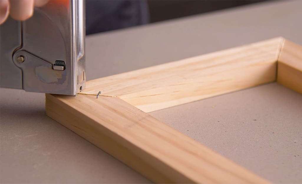 A wood frame is stapled using a staple gun.