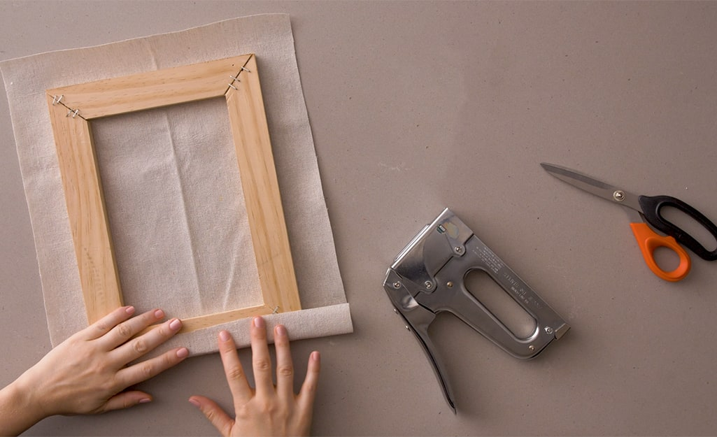 A cut drop cloth is being measured to a frame.