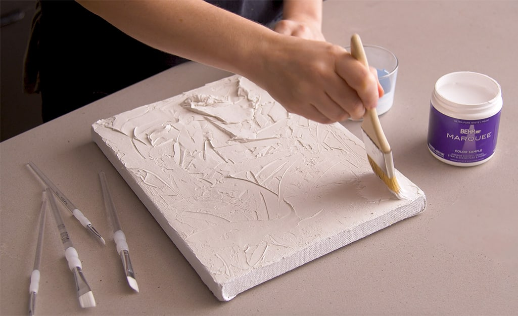 White paint is applied over putty on a canvas.