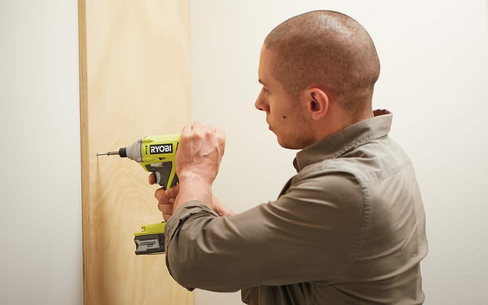 Man using a drill to screw a board to the closet wall.