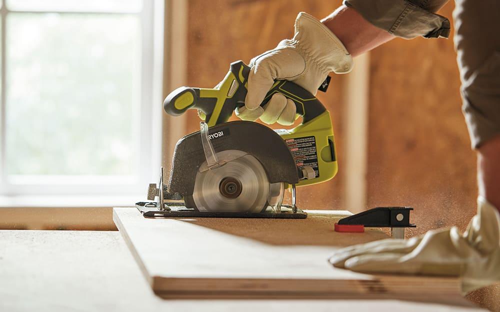 Man using a circular saw to cut a shelf for the closet organizer.
