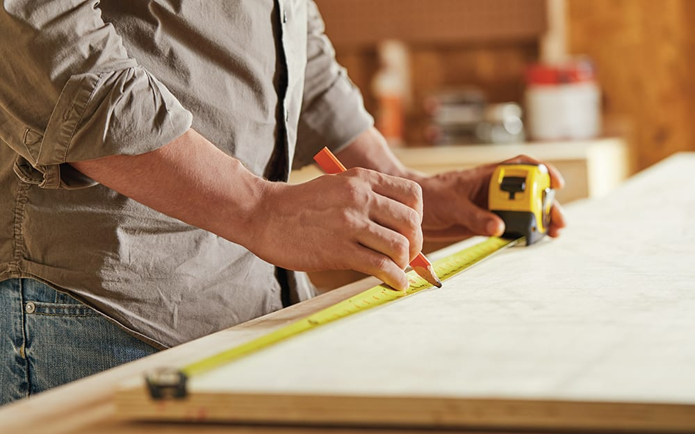 Man measuring wood for the closet organizer.