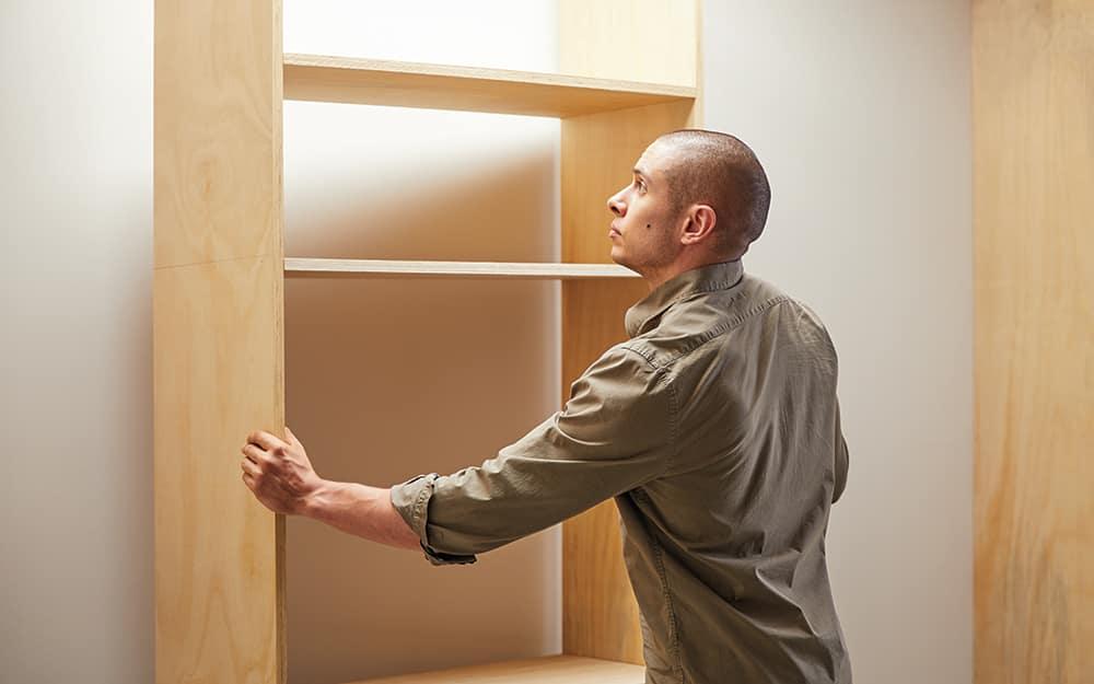 Man positioning his DIY closet organizer against the wall.