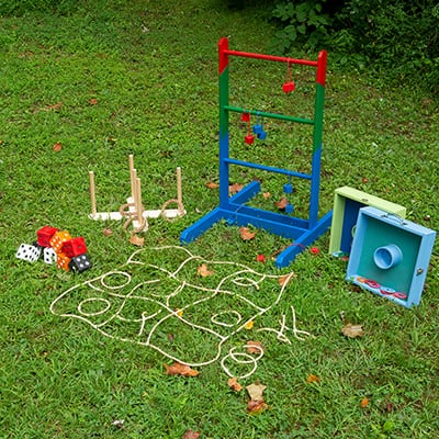 Five different types of lawn games displayed in a yard.