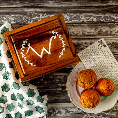 A wood recipe box on a table with a plate of muffins.