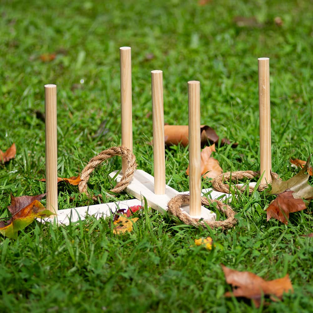 A wooden ring toss game with rope rings on a lawn.