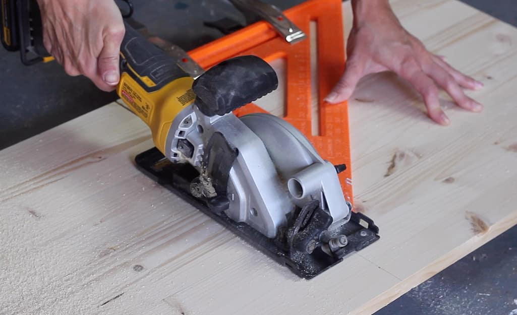 A saw cutting into a piece of wood.