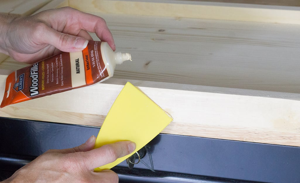 Person patching nail holes in wood.