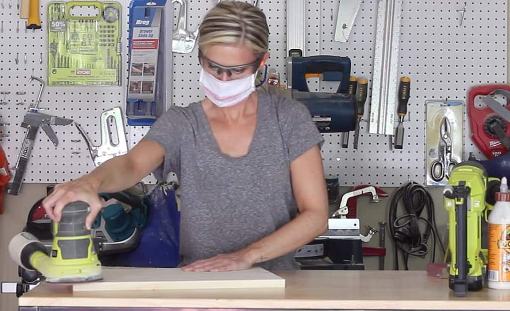 Person sanding a piece of wood.