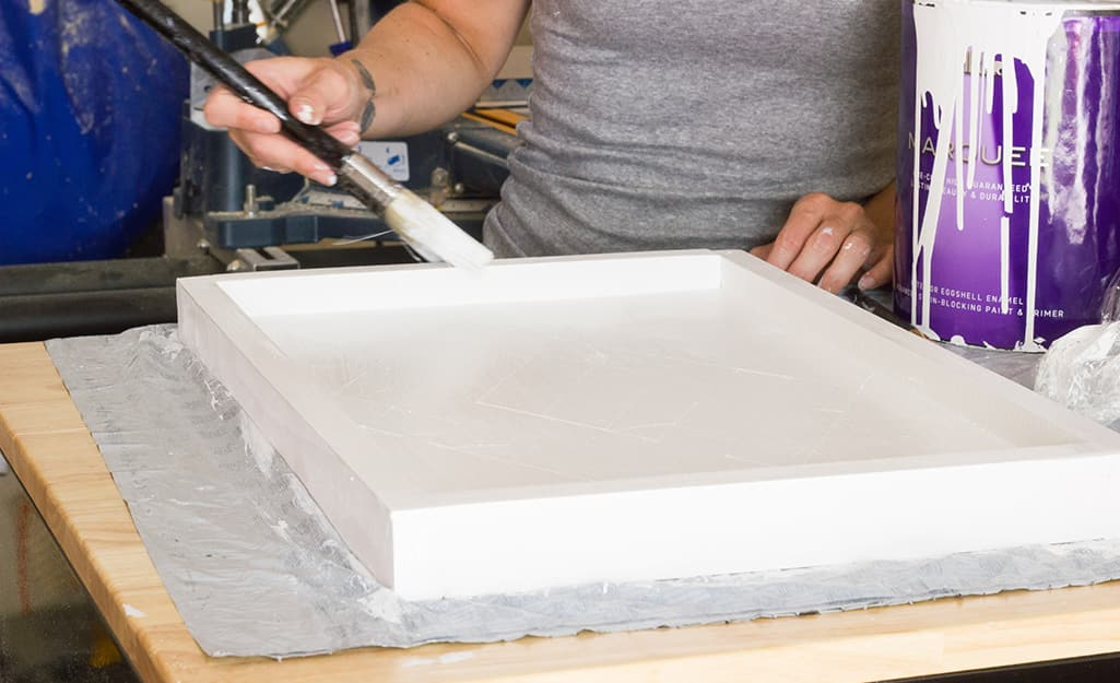 Person paints the assembled wood tray.