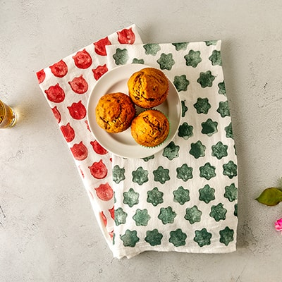 Custom stamped tea towels on a table with a plate of muffins.