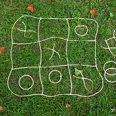 DIY string tic tac toe laying on a lawn.