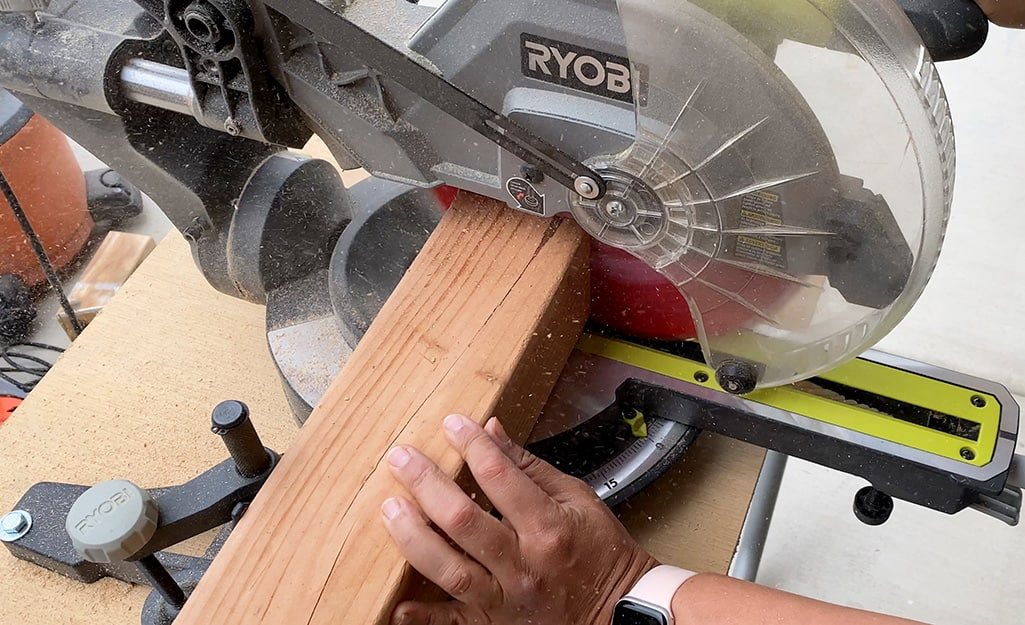A person uses a miter saw to cut 4 x 4 boards.