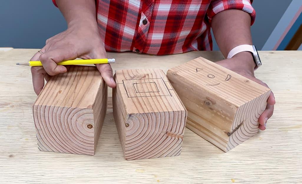 Three wood blocks has Santa designs drawn on them.
