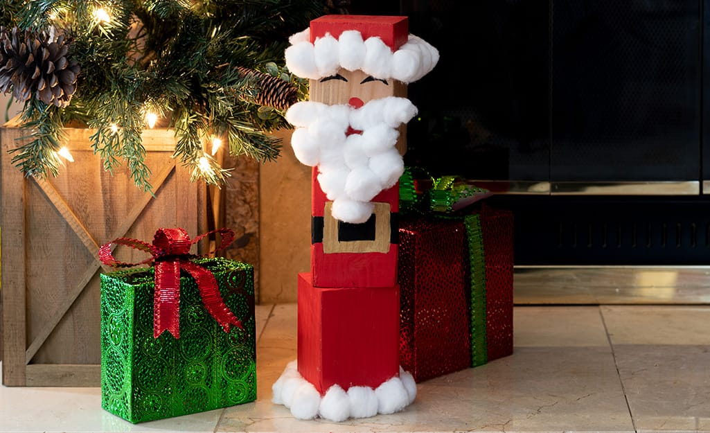 A completed wood block Santa sits near a Christmas tree and presents.