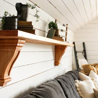 A Varathane premium stained wood shelf hangs on a white shiplap wall.