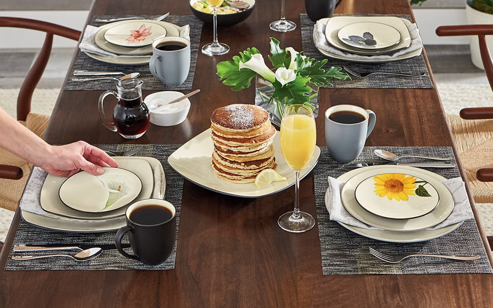 Four casual place settings at a breakfast table with pancakes.
