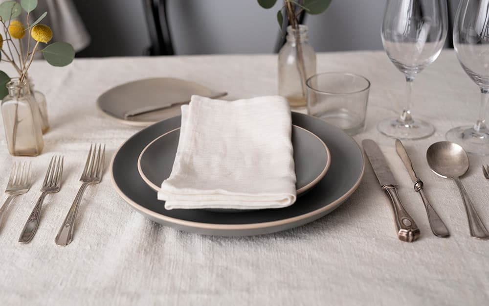 A formal place setting with the napkin on top of the plate.