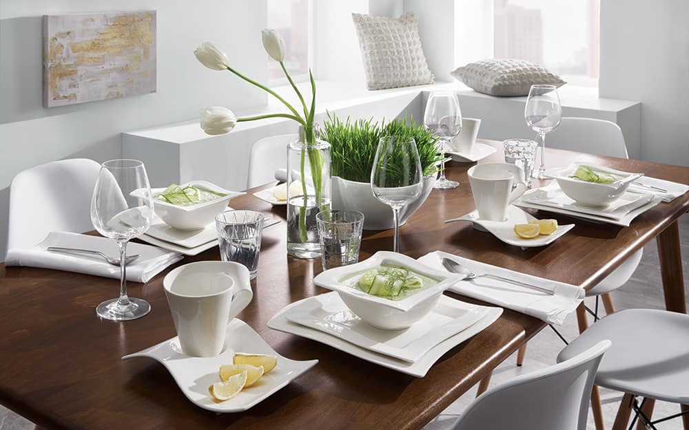 An elaborate dining table set with white dishware.